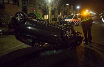 Auto over de kop op Travertijndijk in Roosendaal